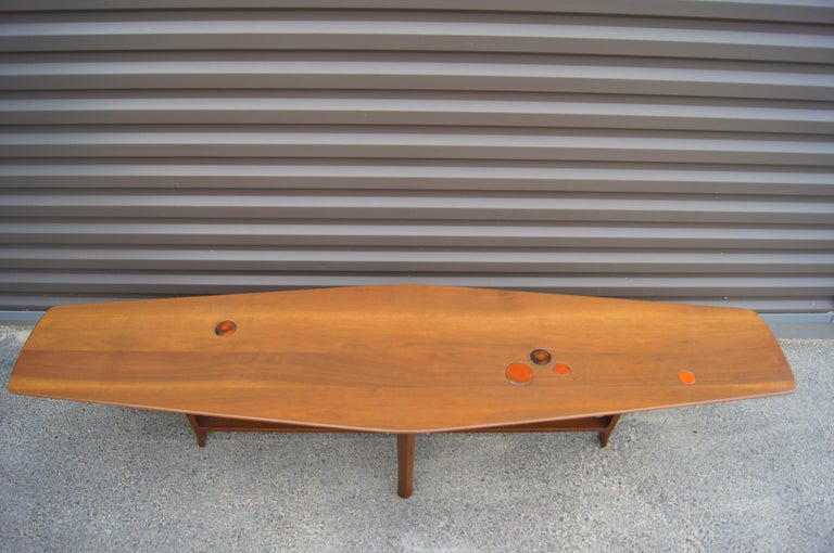 Edward Wormley designed this fabulous walnut coffee table, model 5632N, for Dunbar circa 1957. The long, angular top is inset with orange and black ceramic tiles by Gertrud and Otto Natzler and floats over a cross-frame base with a darker,