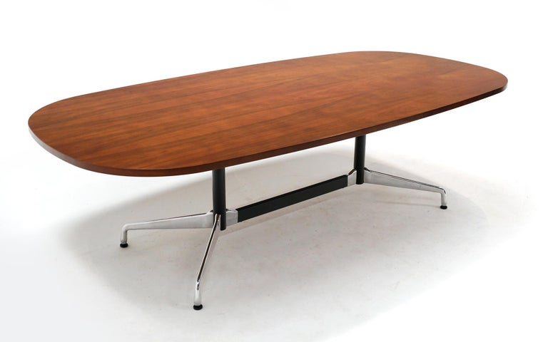 Eight foot long walnut dining / conference table designed by Charles and Ray Eames, manufactured by Herman Miller. Signed with the Eames Herman Miller label. This table was produced in the 2000s and is in very good condition with only a few light