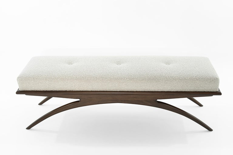 Artfully balanced. This handcrafted bench has a lightweight aesthetic with solid construction. The prim, rectangular cushion is beautifully upholstered in soft bouclé, resting delicately on a solid walnut base. Elevate your space with sloping curves