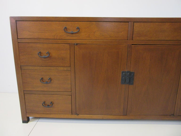 A rich medium colored walnut credenza / cabinet with six smaller drawers to each side , two larger top drawers and two middle doors with a shelve and storage . All having satin black metal pulls and retains the original hanging paper tag from the