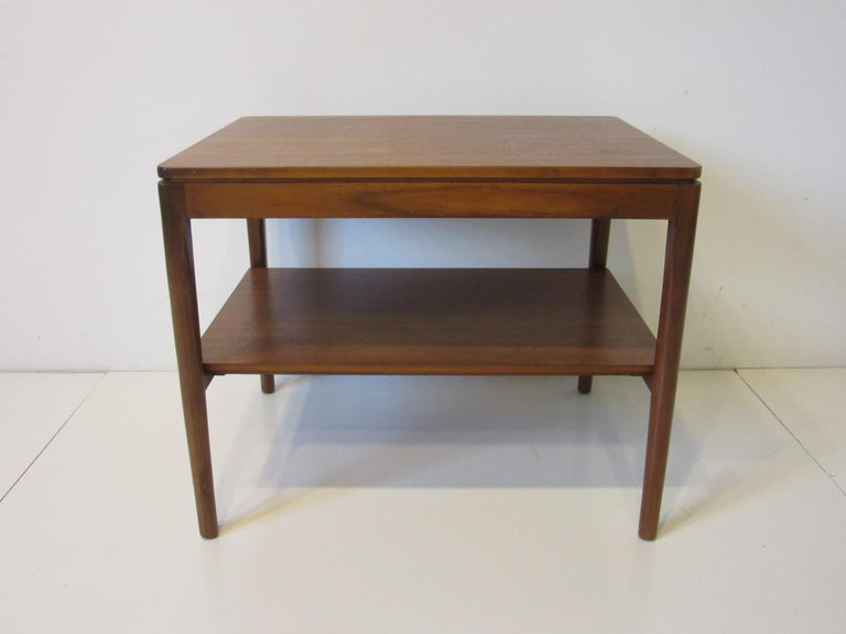 A walnut side table with solid construction designed by Kipp Stewart for Drexel from their Declaration collection, a simple design with rounded edges and fine wood gaining. Retains the manufactures stenciled model and manufactures information.