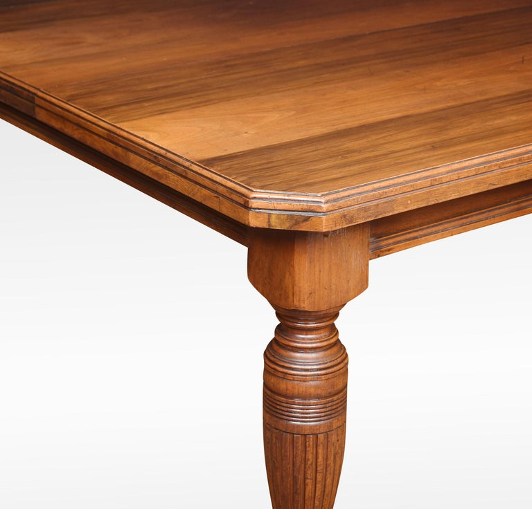 19th century walnut dining table, the rectangular top with canted corners and moulded edge. The telescopic action opening to incorporate large leaf. Raised up on turned tapering legs with ceramic casters. Dimensions: Height 29 inches Width 48