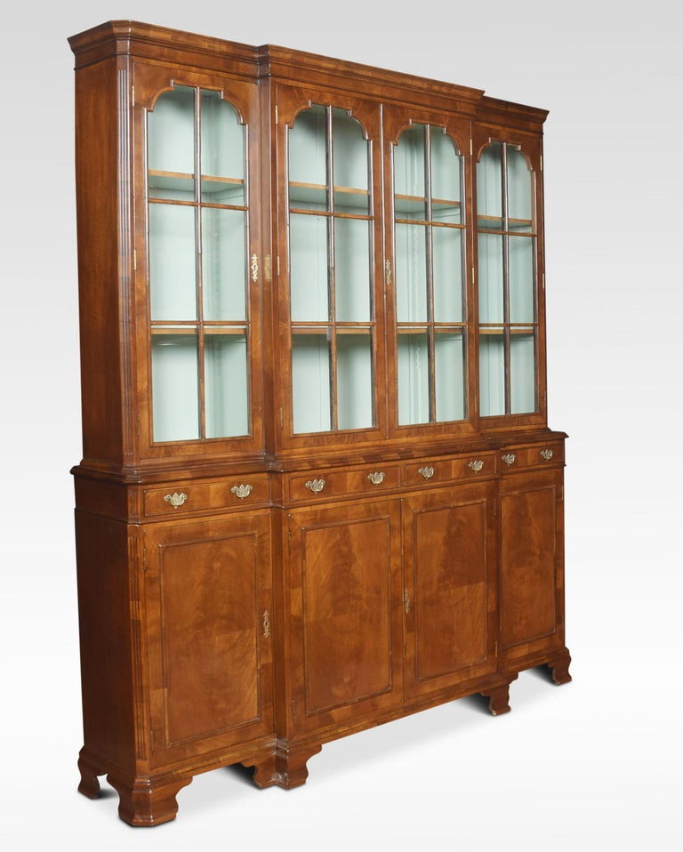 Queen Anne revival walnut four-door bookcase, the projecting cornice above, four large glazed doors opening to reveal an adjustable shelved interior. To the base Dimensions Measures: Height 82.5 inches Width 71.5 inches Depth 15 inches.
