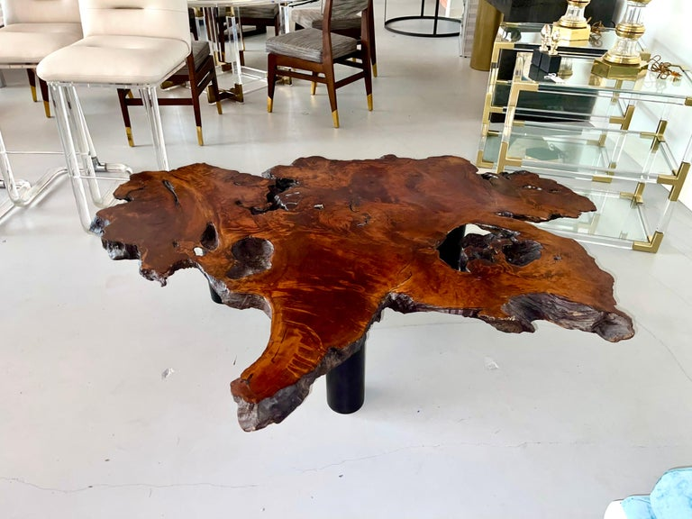 A vintage massive walnut slab from the 1970's. We had the top stripped of the heavy epoxy resin finish and had a new base fashioned of three steel legs painted a flat black. Great organic form and wonderful graining. Natural void ares on the top