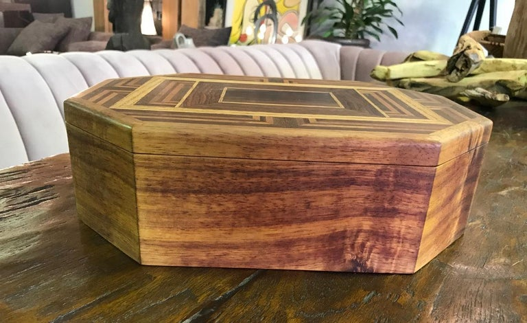 Beautiful craftsmanship and design.  This eight sided box is made and inlaid with multiple types of wood including walnut, oak, Koa, mahogany and hinges made of Brazilian rosewood. It has multiple internal compartments.   Dimensions: 4.25