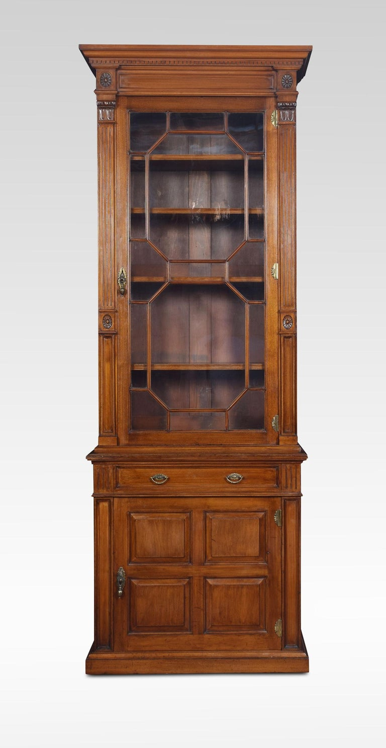 Walnut pier bookcase of narrow proportions, in the manner of Howard & Sons. The dentil cornice above an astragal glazed door enclosing adjustable shelved interior. Flanked by reeded pilasters with lotus capitals. To the base with a frieze drawer and