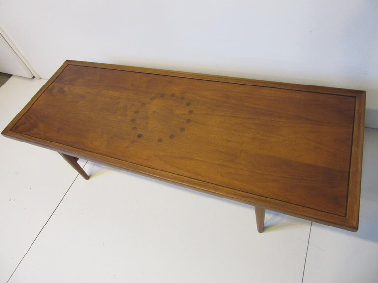 A medium toned walnut coffee table with rosewood dot design to the center of the table having inlay rosewood inset to the edge giving this well crafted table a high end Mid Century feel . Manufactured by the Drexel Furniture company for their