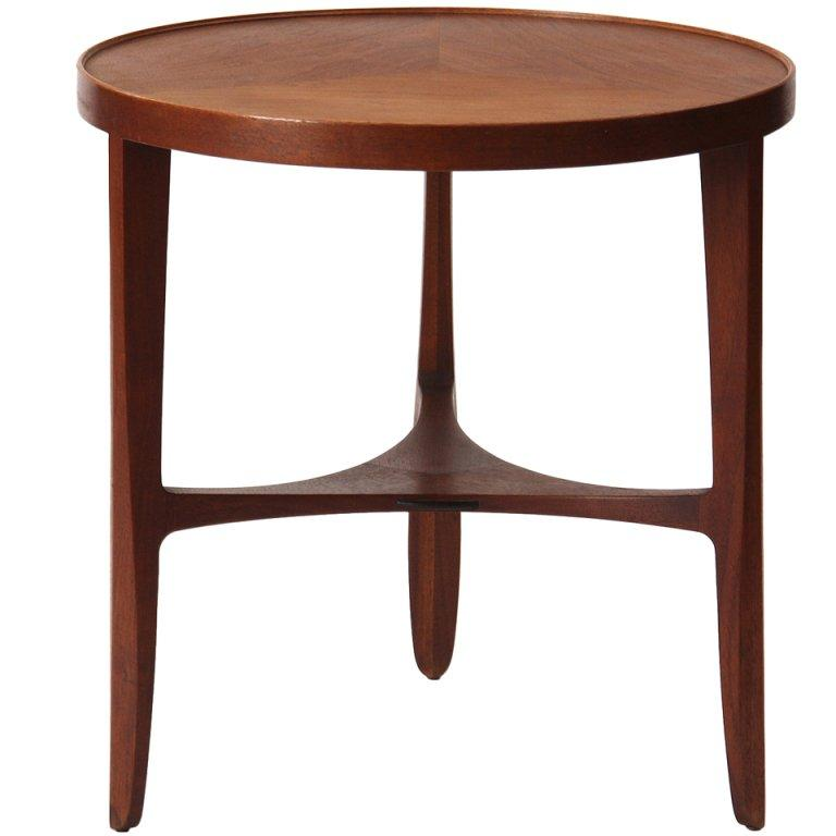 A Mid-Century Modern round-topped side table in figured oiled walnut having sculpted and tapered legs and an organic shaped lower stretcher. Designed by Edward Wormley, manufactured by Dunbar in the USA, 1950s.