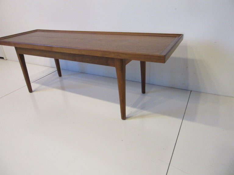 A hard to find smaller scale medium toned walnut coffee table with rosewood inlay detail to the inside edge. This piece is perfect for a tight or small space manufactured by the Drexel Furniture company designed by Kipp Stewart for the Declaration