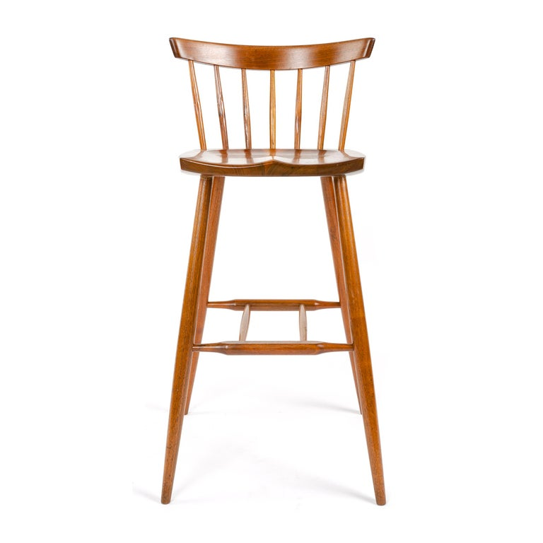 A walnut barstool designed by American Craftsman Master George Nakashima with hand-hewn spindles supporting a thin backrest, a shaped seat on four splayed, and tapered dowel legs with a footrest stretcher. Made by the George Nakashima Studio in the