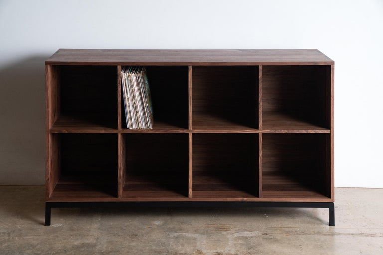 The Max Audio Storage Credenza has sleek lines and modern use of traditional joinery to act as an LP lovers vinyl record storage and a surface for audio equipment. Images shown are in Walnut Wood with Black Steel Base. Solid and plywood materials