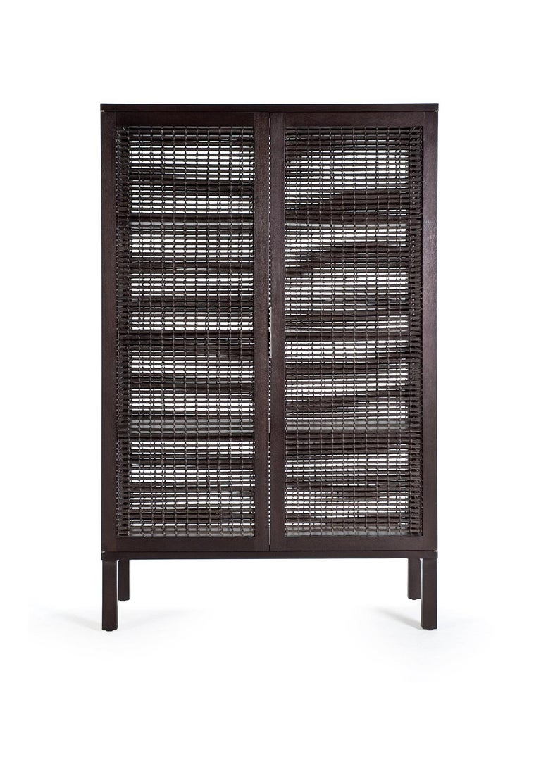 Walnut Suzy Wong cabinet by Kenneth Cobonpue. Materials: Lampakanai, rattan, walnut.  Also available in maple. Dimensions: 50 cm x 100 cm x H 160 cm  Woven panels create a feeling of intimacy as you and your guests indulge in conversation or