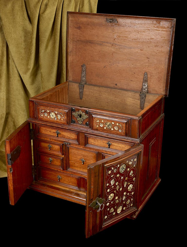 A walnut table cabinet, English, circa 1670; profuse mother of pearl and bone decoration to the doors and the top lid; the doors open to reveal an arrangement of 8 draws; the cabinet measures 21 ½ inches wide, 18 ½ inches tall and 14 inches