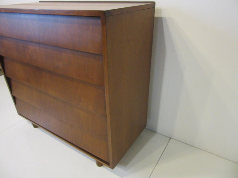 A walnut tall dresser / chest with five drawers with slanted fronts and a raised lip to the top back edge in the manner of Florence Knoll sitting on rounded legs, storage that makes a statement.