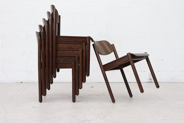 Dark walnut toned stacking wood chairs lightly refinished with cylindrical legs and curved backrest. Beautiful color and elegant style in conveniently stackable dining chairs. In original condition with some wear and consistent with their age and