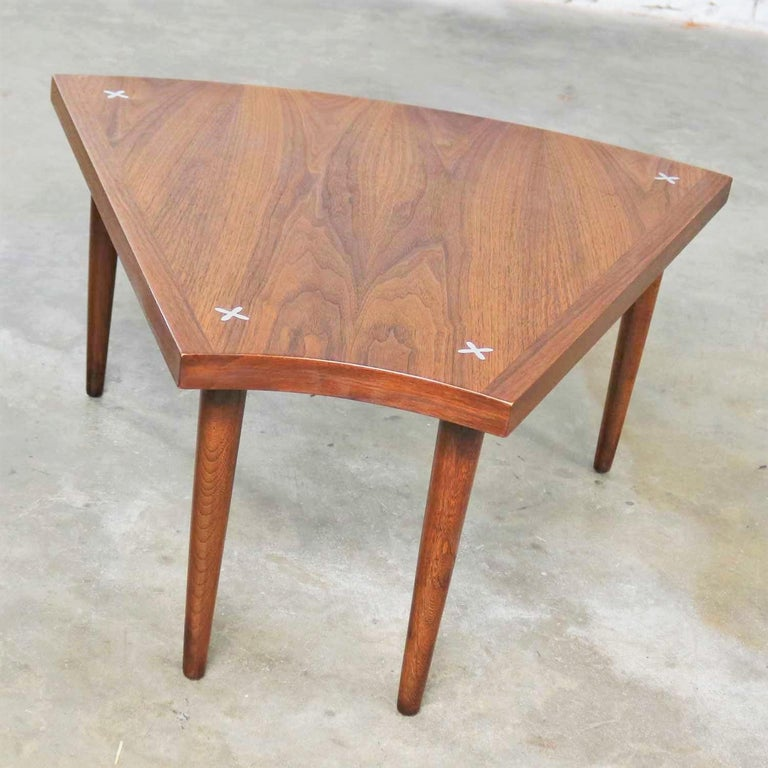 Handsome wedge or pie shape end, side, or occasional table in walnut with inlaid aluminum X's attributed to Merton Gershun for American of Martinsville. It is in wonderful vintage condition. The top has been restored and is beautiful, but it still