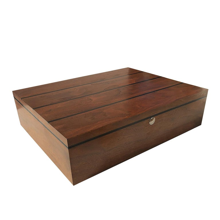 Stunning in its simplicity, this rectangular box is handcrafted of solid American walnut wood with an insert of African ebony wood placed lengthwise on the top. The interior is lined in red velvet and can be customized on request with removable