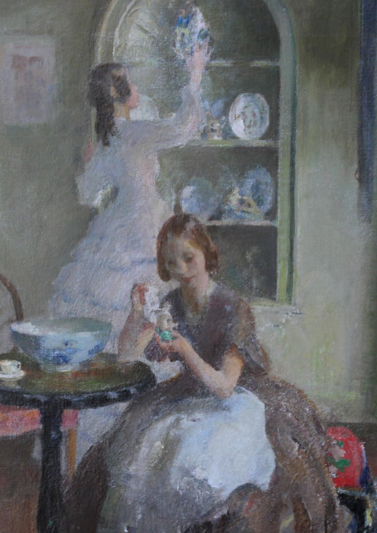 This charming oil painting is by noted British Impressionist portrait painter Walter Ernest Webster.  The painting depicts two young women cleaning the china together and was painted circa 1930. This period oil painting is a beautiful scene he