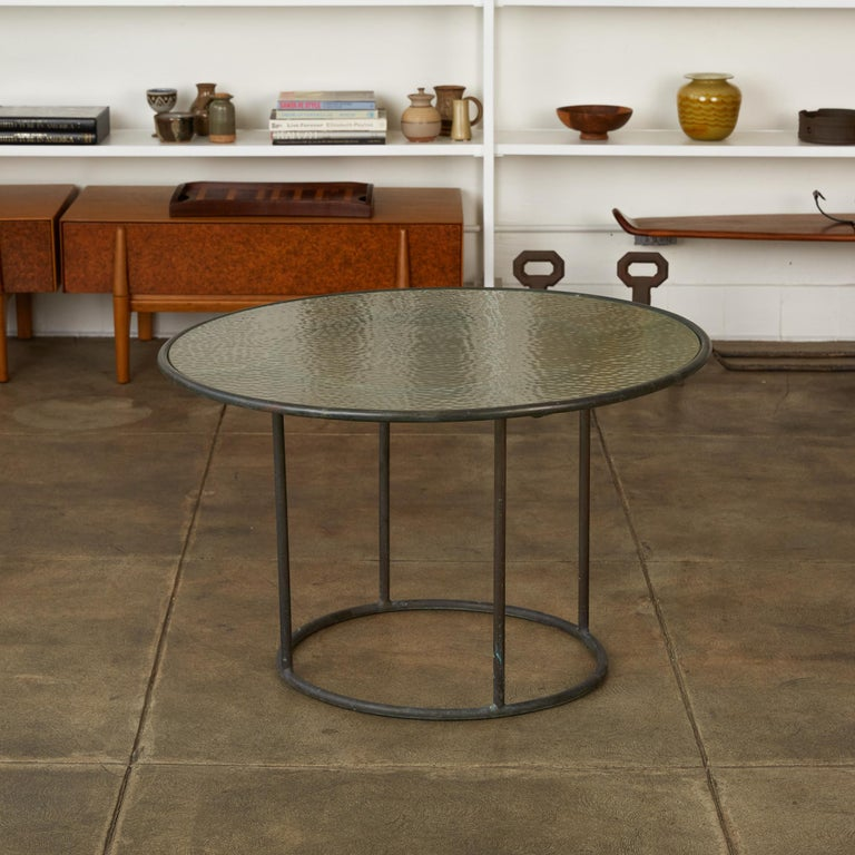 A patio coffee table in patinated bronze designed by Walter Lamb and produced by Brown Jordan. The frame is described by two concentric rings of bronze with radial supports and a circular bronze base. The round tabletop is a single piece of hammered