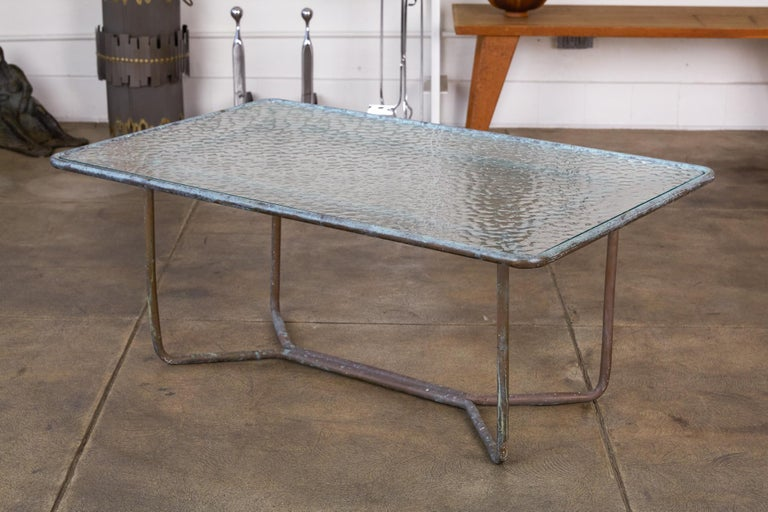 A patio coffee table in patinated bronze designed by Walter Lamb and produced by Brown Jordan. The table has a rectangular shape with rounded corners, supported by bunt tubular in matching bronze. The legs are joined by diagonal stretchers and a