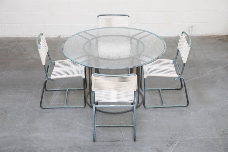 This highly-sought-after and collectible dining set comprised of four bronze dining chairs and a 48.5