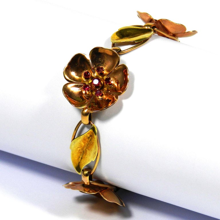 Walter Lampl Retro 14 K gold ruby flower bracelet, circa 1940  A rare two-tone Retro flower bracelet from New York's jewelry designer Walter Lampl.  Its design comprises three rose gold blossoms set with rubies, which alternate with oval links,
