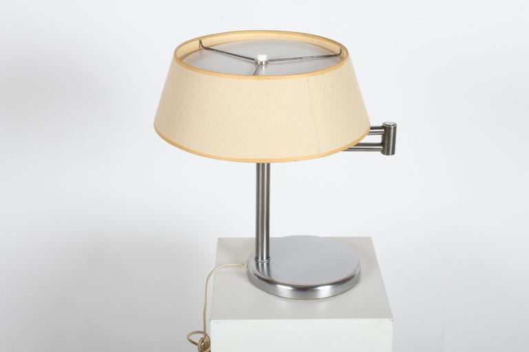 Listed is Walter Von Nessen's most famous lamp, which he designed in 1930s. This swing-arm Classic in brushed nickel is in very nice condition, and production date is sometime in the late 1950s. Has original linen shade, white reflector disc, and S