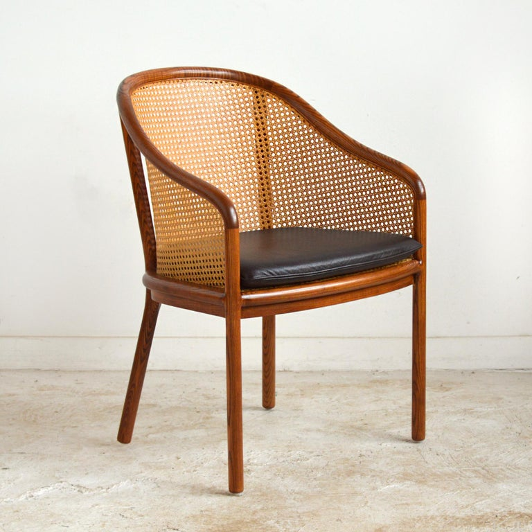 Ward Bennett's designs for Brickel are refined and understated with a exceptionally high degree of craftsmanship. These ash framed armchairs have cane back and seat supports with a loose seat cushion. The graceful lines and natural colors and