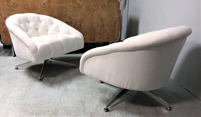 A pair of swivel chairs design by Ward Bennett and edited by Lehigh Leopold. They have a low modernist profile and an provocative inviting presence. The bases are a highlight of this design, solid thick gracefully robust aluminum that extend at a
