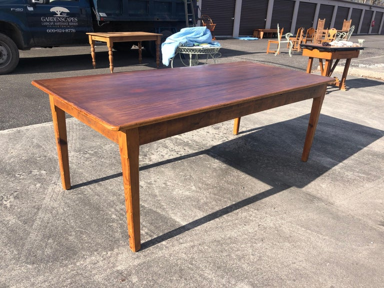 An almost 7 ft long rustic salvaged pine farm table having beautiful plank top with great character including natural worm holes and handsome grain. There are four simple tapered legs.  Apron height from floor 24.75