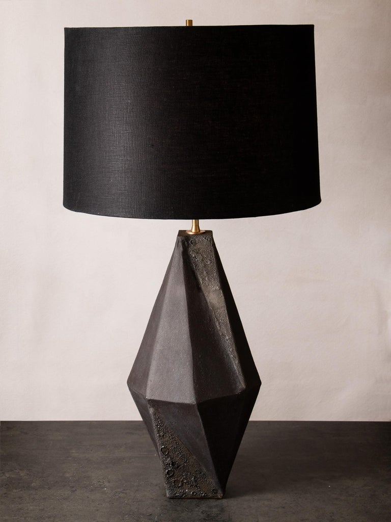 This dramatic black ceramic table lamp features a complex geometric shape, accentuated by contrasting matte black and textured black glazes. Each piece is individually handmade and entirely unique. The lamp is finished with raw brass hardware and a