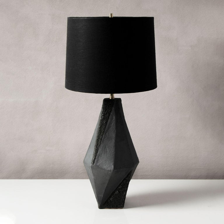 This dramatic ceramic table lamp features a complex geometric shape, accentuated by contrasting matte white and textured black glazes. Each piece is individually handmade and entirely unique.   Available in two colors, with a white or black linen