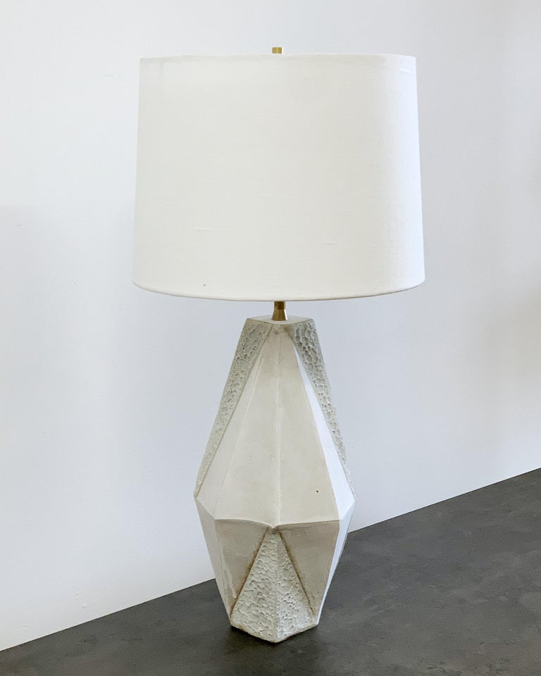 This dramatic ceramic table lamp features a complex geometric shape, accentuated by contrasting matte white and textured white glazes. Each piece is individually handmade and entirely unique.   Available in two colors, with a white or black linen