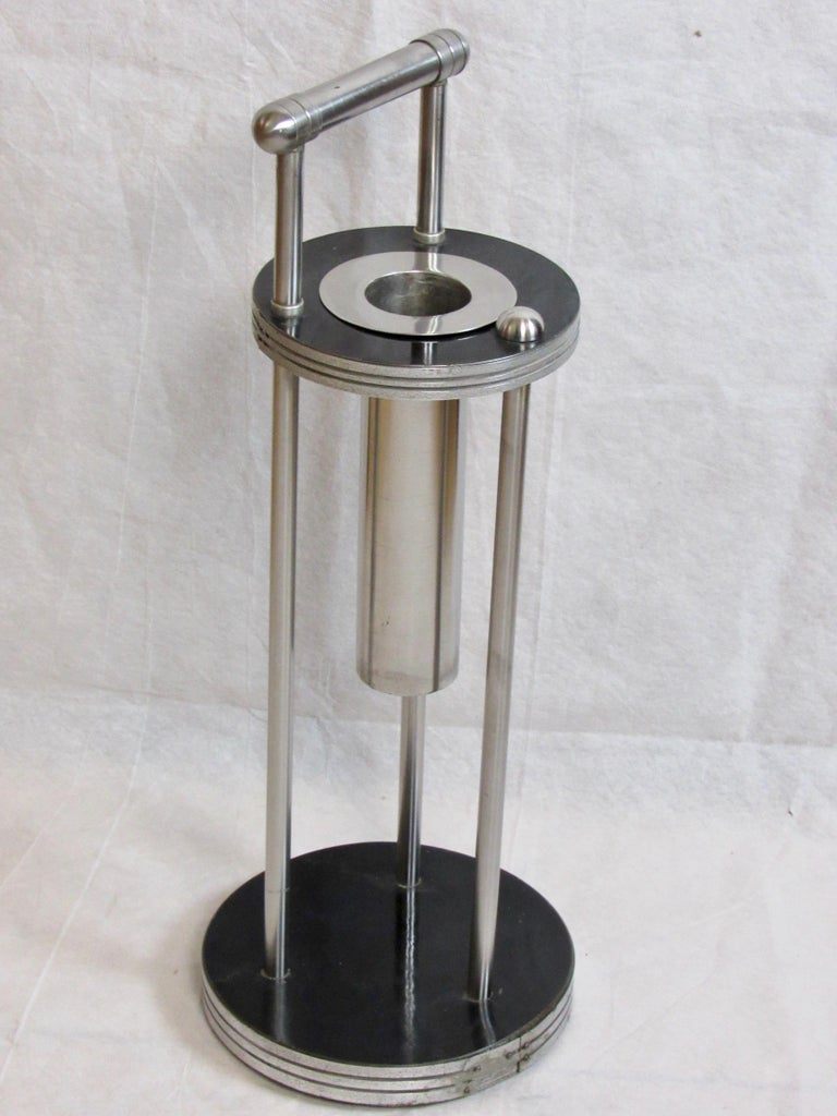 A Warren McArthur smoking stand framed in stainless steel from the early mid 1930's with A Rome, New York