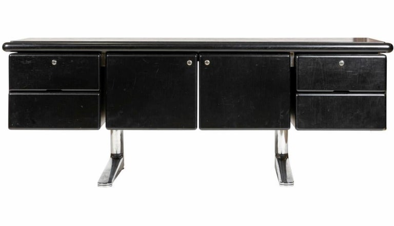 Handsome black oak sideboard designed by Warren Planter and manufactured by Knoll International, in 1973. Entire piece rests on top of two cantilevered chrome legs. 2 drawers flank each side of the sideboard with a cupboard in the middle. Entire