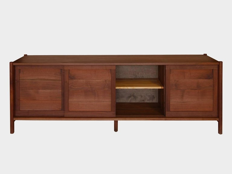 New York Heartwoods' contemporary black walnut credenza is influenced by Mid-Century Modern design and fabricated from solid wood, save the ebonized FSC paneled back. Each cabinet has great storage capacity and is comprised of four artfully