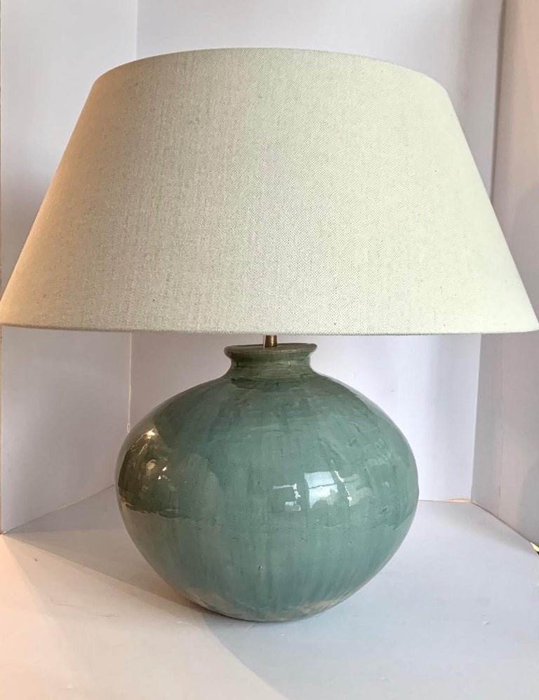 Contemporary Chinese pair of washed turquoise lamps. The turquoise glaze has the appearance of being washed. This gives the finish slightly varied degrees of the turquoise color. Round