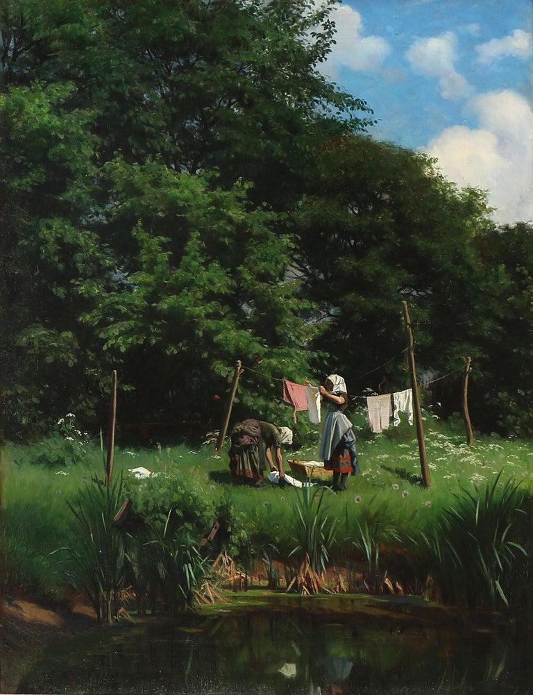 Viggo Pedersen 1854-1926: Beautifully detailed oil painting by Viggo Pedersen of Washerwomen drying clothes by the lake. Signed on exhibition label on the stretcher Viggo Pedersen. Oil on canvas. 63×82 cm. Period frame. Pedersen was born in
