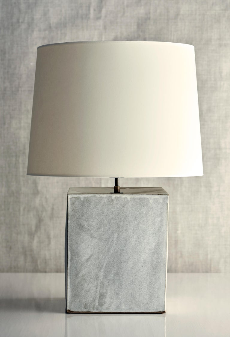 Description  Handmade stoneware slab construction. Lamps are individually crafted and one of a kind.  Finish  Parchment glaze. Antique brass fittings, dimmer switch on socket. Braided black cloth cord and off white paper shade.  Dimensions  Lamp