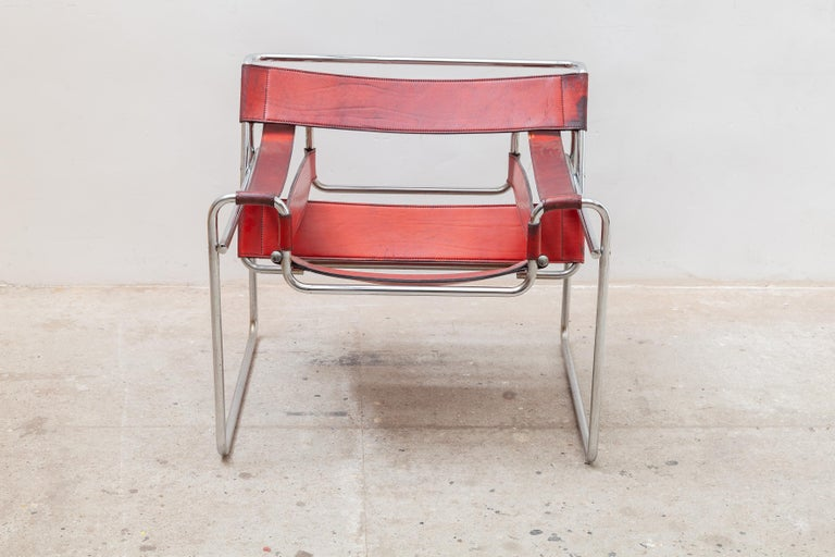 Wassily B3 armchair in red leather, original design from 1925 by Marcel Breuer manufactured in the 1970s. Polished chrome metal tubular frame and original armrests, back and seat. The leather is in good condition with some wear from use with a nice
