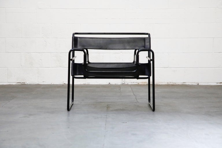 This authentic model B3 'Wassily' lounge chair by Marcel Breuer for Knoll International is a rare black on black colorway featuring a black tubular steel frame and thick black leather slings that make up the seat, arms and seat back. While many