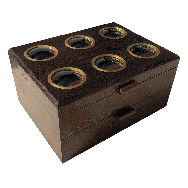 Handmade of wengè wood with brown leather interior, this box is not only a functional object to protect collectible watches from scratches and damages, but it is also a superb decorative piece on a bedroom dresser or office desk. A simple, classic