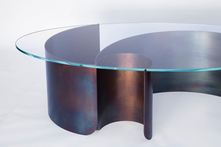 Rolled sheets of steel curl and peel away beneath a transparent oval glass surface, capturing the dynamic moment of a cresting wave. The vibrant multicolored steel surface is created through a unique heat treatment process through which molecules