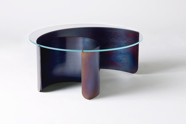 Rolled sheets of steel curl and peel away beneath a transparent glass surface, capturing the dynamic moment of a cresting wave. The vibrant multicolored steel surface is created through a unique heat treatment process through which molecules realign