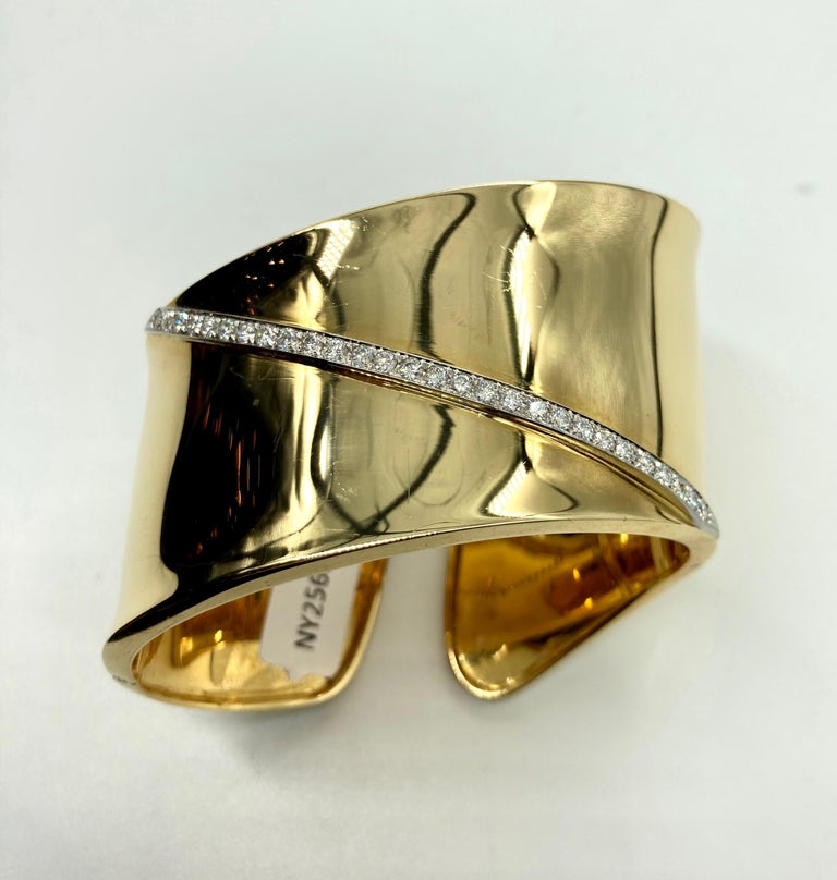 A chic 18 karat yellow gold cuff bracelet of wavy design with 0.85 carats of diamonds. Weighs 75 grams.