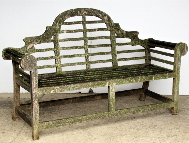A very high quality vintage teak Lutyens style garden bench with wood pegged construction in the best aged weathered surface profusely encrusted with old algae lichen growth. Best guess this bench dates from the last quarter of the 20th century.