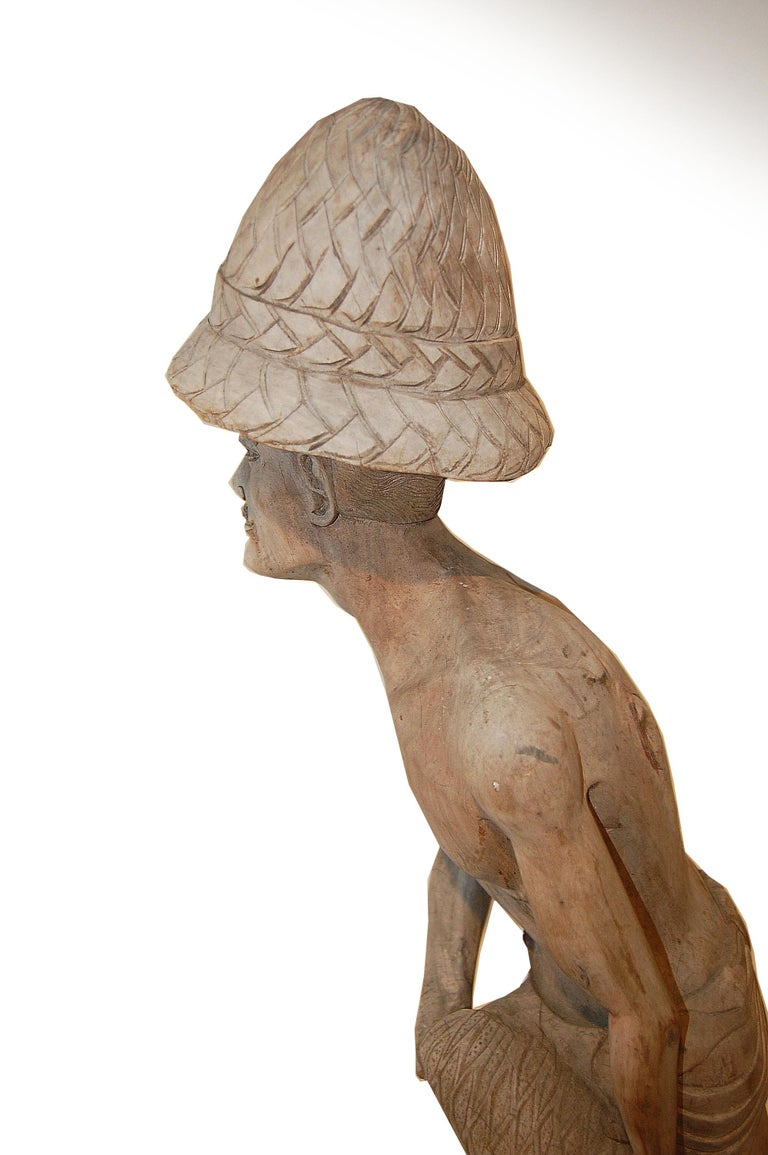 Every so often we encounter figures such as this sculpture, of a man holding a fishing net, that simply command our attention. The sculpture shows evidence of the wood giving way to the elements in the face, torso, shoulder, and has a missing