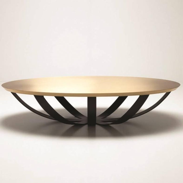 As the name suggests, the Web coffee table's base resembles a spider's web. The brushed brass top complements the metal base.  The oval table offers a generous table top without blocking the floor surface.  Handmade craftamanship for a great