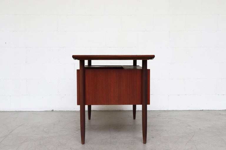 Beautiful WeBe style dark teak desk with organic drawer pulls, floating top and exposed bookcase on the back side by Tijsseling for Hulmefa. In good original condition, wear in keeping with its age and usage.