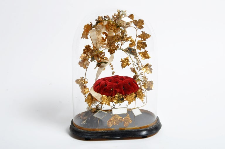 Quite the curiosity, this glass dome is more like a time capsule. Inside of the glass dome is an upholstered cushion with a frame and legs made of gilt foliage, porcelain flowers, and mirrored glass. A bird-form finial holding a wreath of laurel in